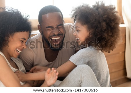 Photo of Happy african american family with cute little kid daughter tickling laughing at home together, cheerful black parents and small child girl having fun playing bonding enjoy funny lifestyle activity