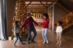 Happy African American family with two adorable kids celebrating Christmas, dancing to music near tree at home together, smiling mother and father with son and daughter enjoying winter holidays