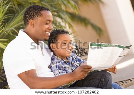 Happy African American Father and Mixed Race Son Having Fun Reading Park Brochure Outside.