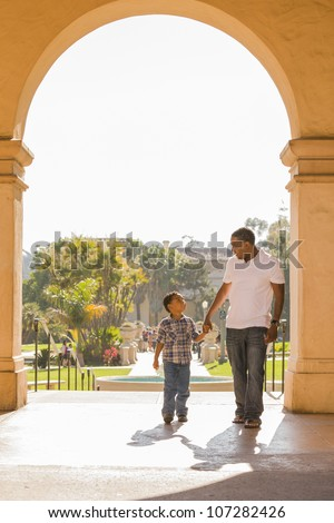 Happy African American Father and Mixed Race Son Holding Hands Walking in the Park.