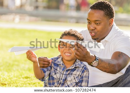 Happy African American Father and Mixed Race Son Playing with Paper Airplanes in the Park.