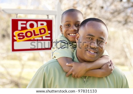 Happy African American Father and Son in Front of Sold Real Estate Sign.