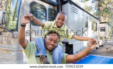Happy African American Father and Son In Front of Their Beautiful RV At The Campground.