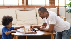 Happy African American Father and son playing chess game in living room together. Family activity and leisure.