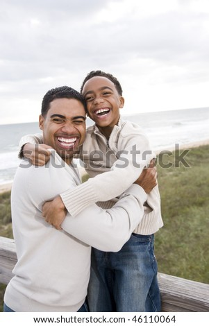 Happy African-American father and ten year old son laughing at beach