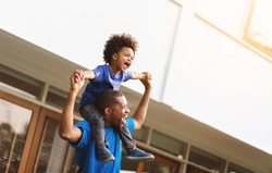 Happy African American Father carrying or piggyback his little son laughing playing and having fun together outside.