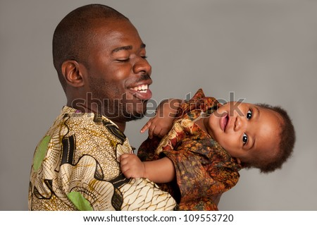 Happy African American Father Holding Baby Playing Isolated on Grey Background