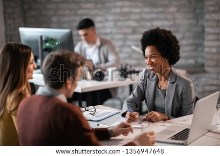 Happy African American financial advisor talking to a couple about their future investment during a meeting in the office.