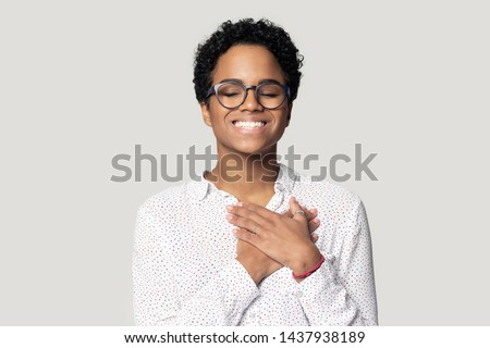 Happy african American girl in glasses isolated on grey studio background keep hands at chest at heart feel grateful, thankful biracial young woman with eyes closed smiling thanking god. Faith concept