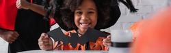 happy african american girl in halloween costume holding paper cut bat near brother, banner