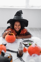 happy african american girl in witch halloween costume carving pumpkin near cookies and candles