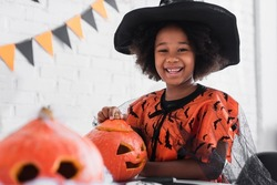 happy african american girl in witch halloween costume near caved pumpkins