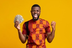 Happy african american guy in traditional t-shirt holding bunch of money and shouting, yellow background