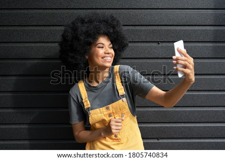 Happy African American hipster woman blogger with Afro hair laughing, holding phone, recording vlog, shooting social media stories or video calling in mobile app standing on black background.