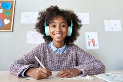 Happy african american kid child girl wearing headphones looking at web cam talking with remote teacher on distance learning video conference call chat class, headshot zoom portrait, webcam view.