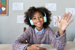 Happy african american kid child girl wearing headphones waving hand talking with remote teacher on social distance learning video conference call zoom class, headshot zoom portrait, web cam view.