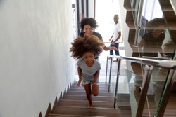 Happy african american kid girl running up stairs into new big house with black parents, excited child daughter having fun exploring own home, afro family moving day concept, relocation, mortgage