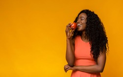 Happy African American Lady Enjoying Red Apple, yellow studio background, copy space