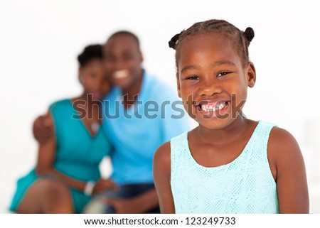 happy african american little girl standing in front of parents