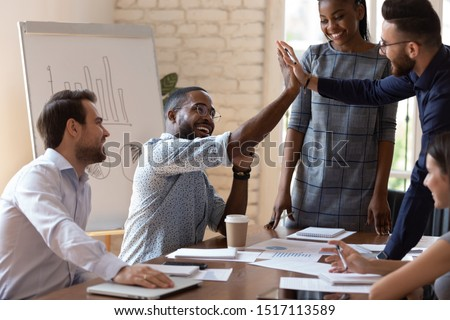 Happy african american male manager sitting at table on business team brainstorming meeting, giving high five to arabian colleague, congratulating with shared teamwork success or good project idea.