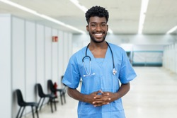 Happy african american male nurse with beard at vaccination station is ready for vacinating patients against coronavirus infection