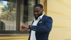 Happy african american male professional walking on street in slow motion. Afro businessman looking at wrist watch. Cheerful african business man checking time.