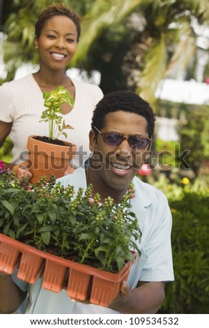 Happy African American man and woman working in the garden