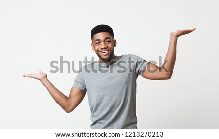 Happy african-american man comparing variants, making scale with his empty hands, copy space