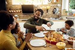 Happy African American man having Thanksgiving lunch with his family and carving stuffed turkey at dining table.