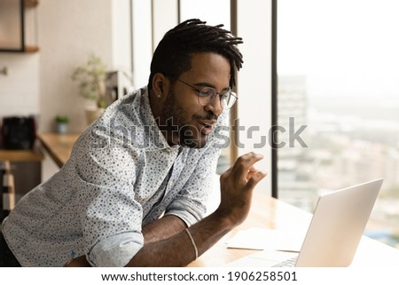 Happy african american man hipster talk by video call in laptop app agree with friend join fingers in ok sign. Young black businessman freelancer receive remote job task online show yes okay to client