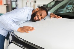 Happy African American Man Hugging Hood Of His New Car, Joyful Smiling Millennial Black Guy Dreaming About Buying Vehicle In Auto Showroom, Leaning At Surface Of Luxury Automobile, Closeup Shot