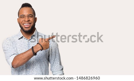 Photo of Happy african American man in glasses and shirt point with finger at blank copy space aside, smiling black male in spectacles isolated on grey background show free advertising place or sale offer