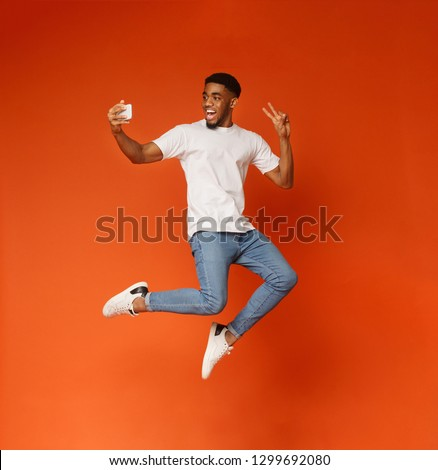 Happy african-american man jumping and making selfie on smartphone, showing peace gesture on orange background