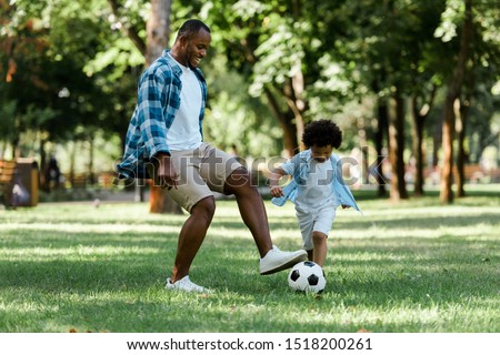 happy african american man playing football with curly son  Photo stock ©