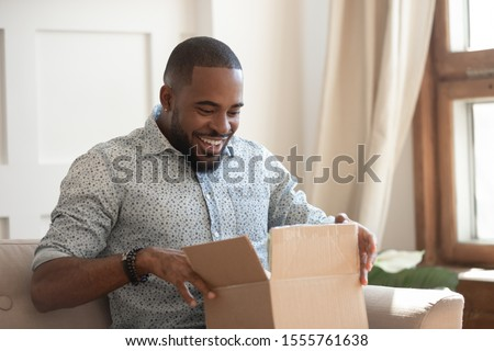 Happy african american man sit on couch feel excited opening cardboard box delivery parcel, smiling biracial millennial male shopping online unpack unbox online order, overjoyed with service or goods