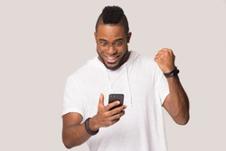 Happy african American man stand isolated on grey studio background hold smartphone feel excited get pleasant message, smiling black male using cellphone win lottery online, receive good offer