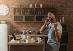 Happy african american man talking on smartphone while baking in kitchen