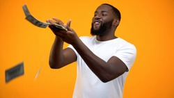 Happy African-American man throwing dollars banknotes, wasting money, concept
