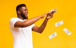 Happy african american man throwing out money banknotes, yellow studio background
