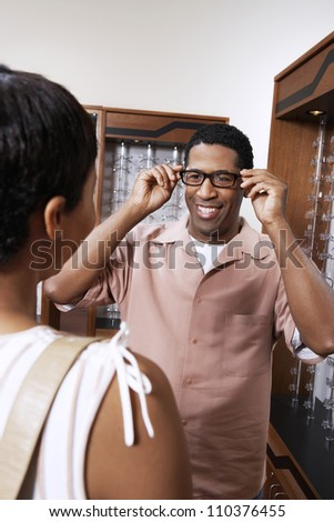 Happy African American man trying on glasses at shop