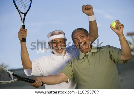 Happy African American man with a friend playing tennis