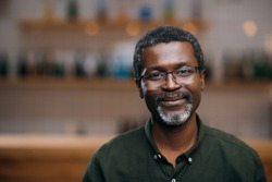 happy african american mature man in front of blurred bar counter