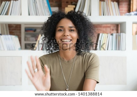 Happy african American millennial woman wave talk on webcam or having conversation, smiling positive black female blogger shoot record new blog or vlog, greeting say hello to followers audience