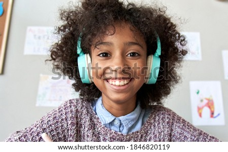 Happy african american mixed race kid child girl wearing headphones looking at camera or web cam remote distance learning on video zoom conference call, virtual class, headshot close up face portrait.