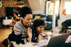 Happy African American mother and daughter using laptop and waving while making video call on Christmas at home.