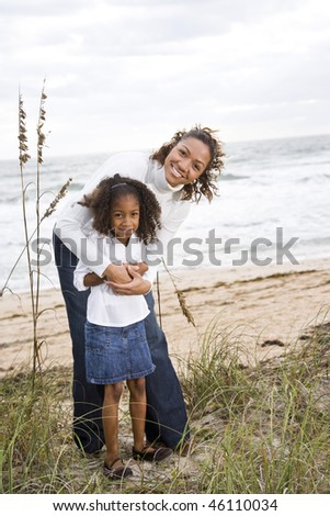 Happy African-American mother and six year old daughter at beach