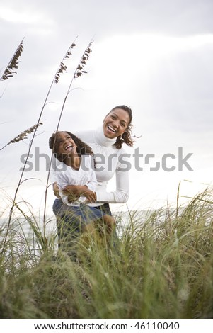 Happy African-American mother hugging and laughing with six year old daughter at beach - stock photo