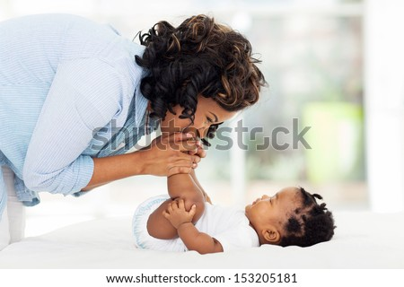 happy african american mother kissing baby feet while playing on bed