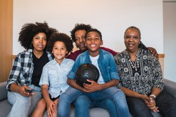 Happy african american multi-generation family watching soccer match on television in living room at home. Family and sport concept.