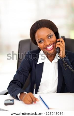 happy african american office worker talking on landline phone